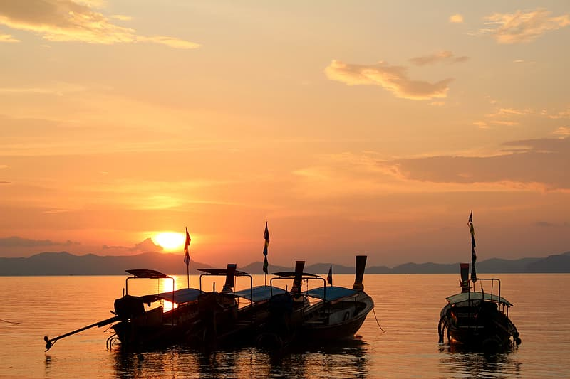 Silhouette of four boats on body of water
