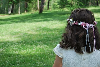 Girl wearing white dress with pink headdress looking towards the trees during daytime