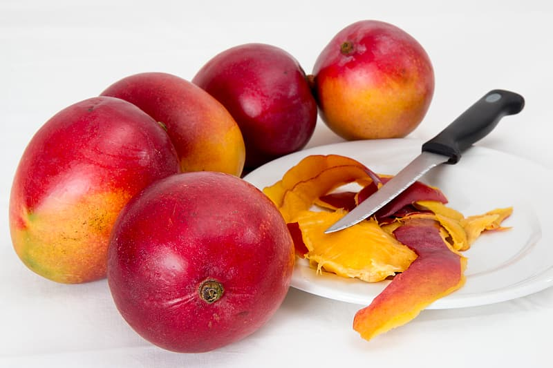 Five red mangoes beside white plate with peeled mango and knife