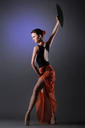 Woman wearing black and orange dress holding folding fan