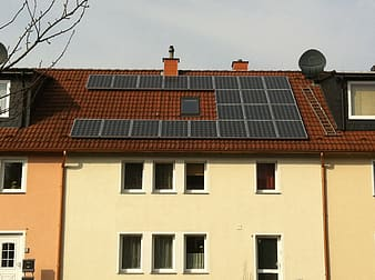 White and brown house with solar panel boards on top of roof