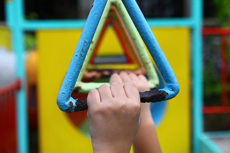 Persons hand on yellow and blue metal frame