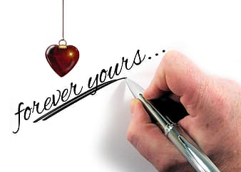 Person writing forever yours on wall