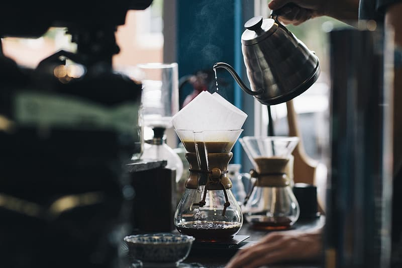 Person pouring coffee on clear glass cup
