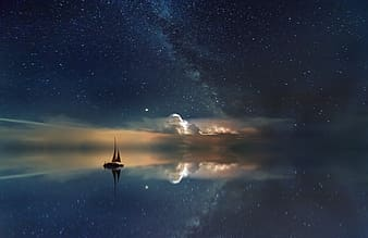Silhouette of person standing on boat on water during night time