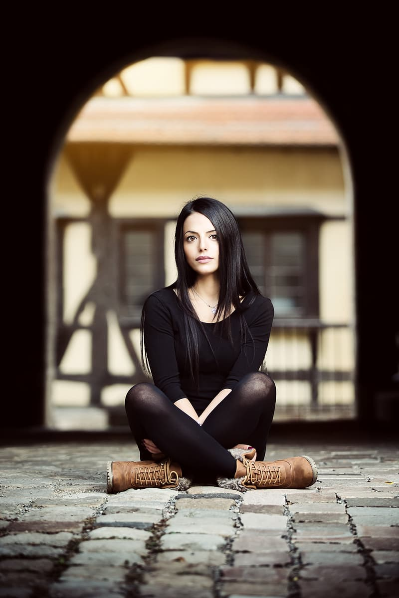 Woman wearing black crew-neck top ad leggings and brown leather boots sitting on grey brick floor