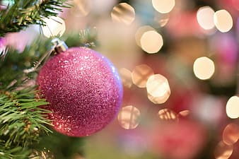 Pink glitter Christmas bauble with bokeh background in selective-focus photography