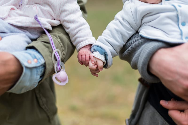 Two babies holding each others hands