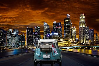 Classic teal car near lighted high rise building during nighttime