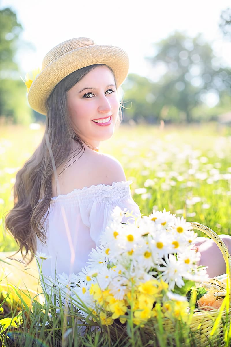 Selective focus photography of woman sitting on grass surrounded by grass and white daisy flowers during daytime
