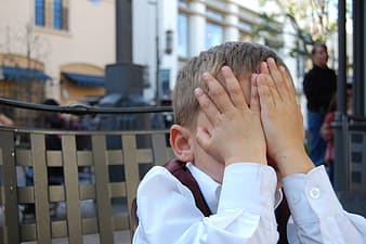 Boy wearing white dress shirt while sitting on chair and close his eyes using his hands during day time