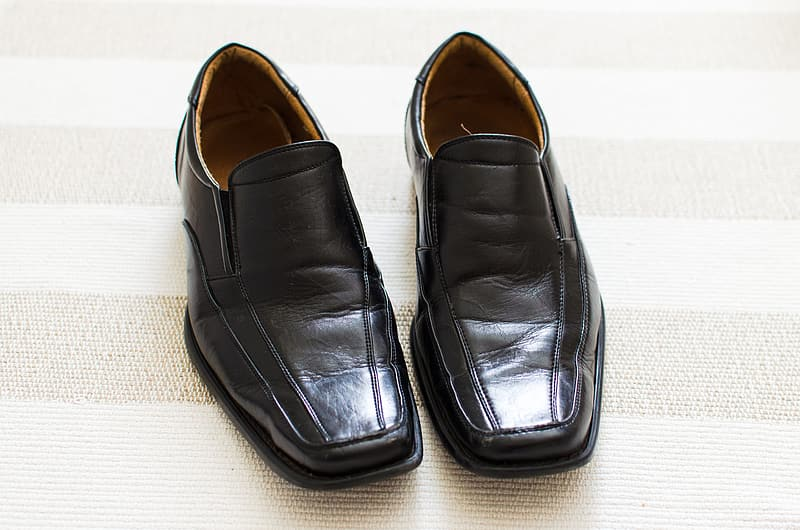 Black leather loafer shoes with white text