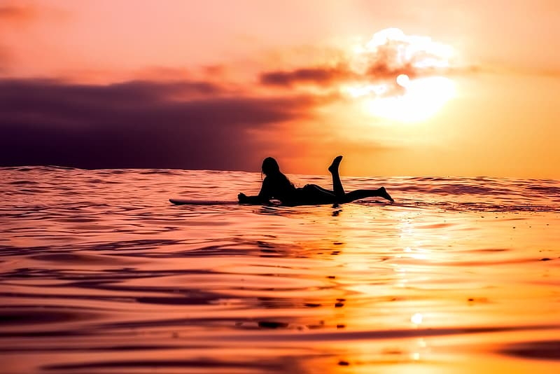 Silhouette of person of surfboard on sea