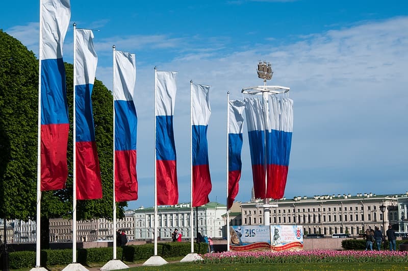 Red-white-and-blue flags over through white buildings