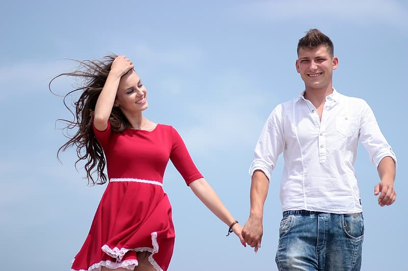 Smiling woman holding hands with smiling man