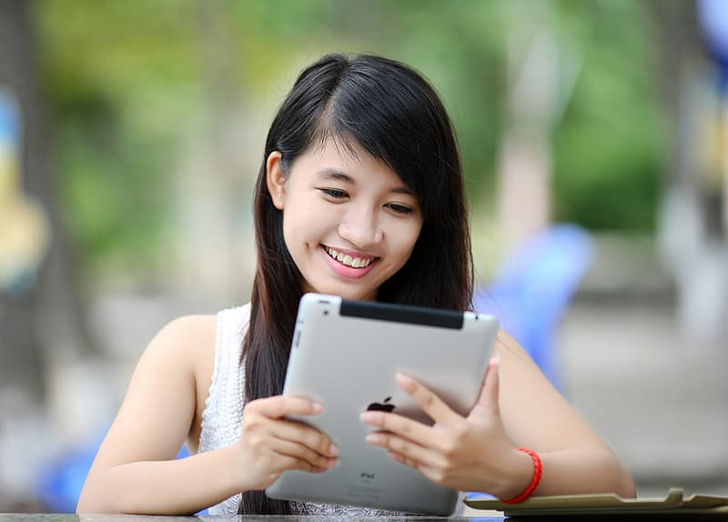 Woman with white floral sleeveless shirt using silver iPad close-up photography