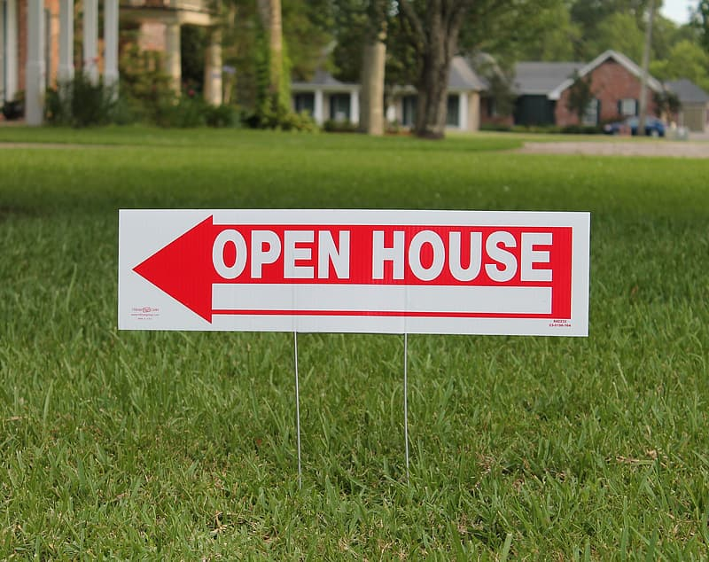 Red and white Open House signage on grass
