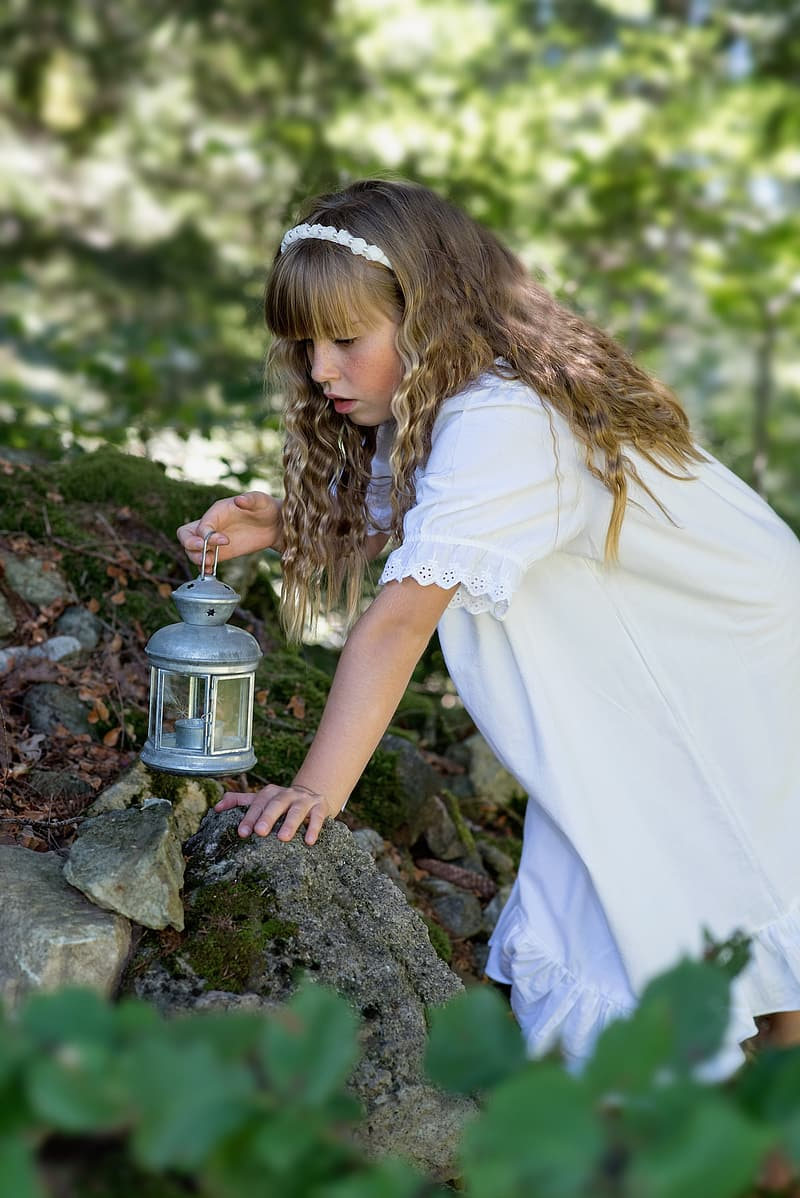 Shallow focus photography of girl wearing white dress holding silver-colored kerosene lamp on her right hand during daytime