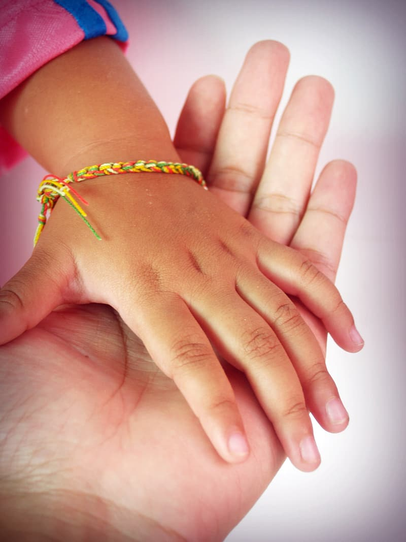 Tilt lens photography of child's hand with bracelet over left palm of person
