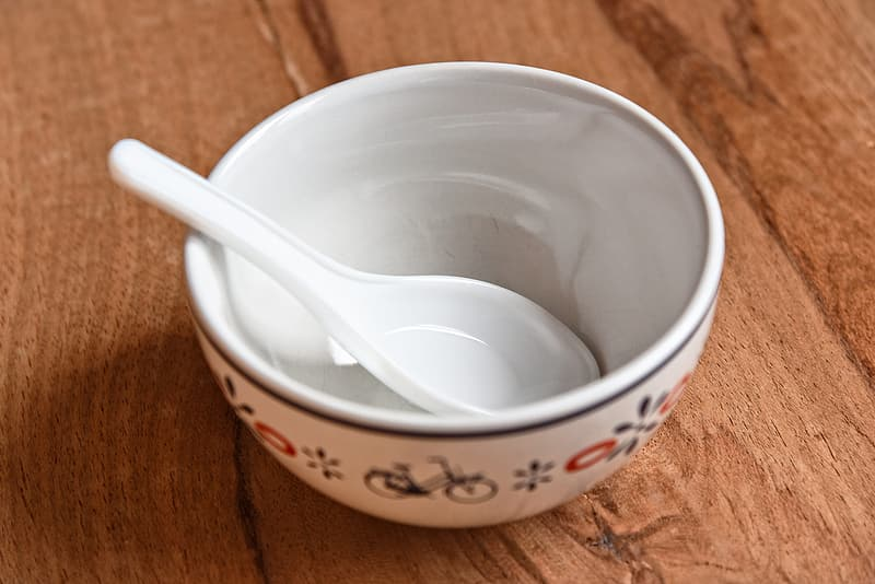 White and red ceramic bowl with silver spoon