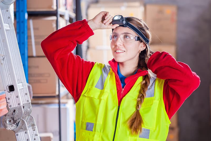 Photo of woman in black headlamp, red long sleeve zip up work suit and yellow work vest