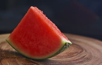 Tilt shift lens photography of sliced watermelon on brown wooden table
