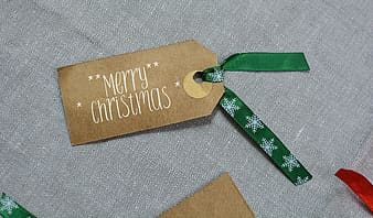 Brown Merry Christmas product tag on gray textile