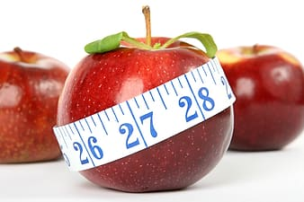 Three red apples with one covered in white measuring tape