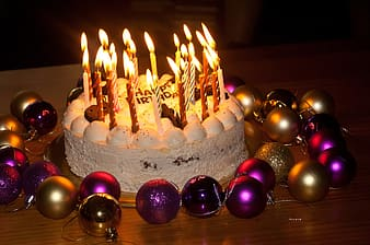 Baked cake with candles and christmas baubles