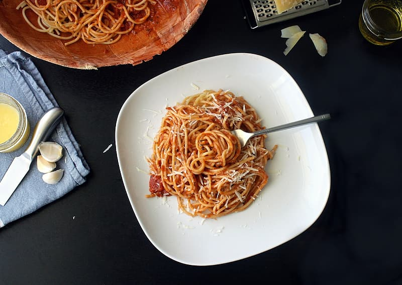 Pasta with red sauce on white ceramic plate
