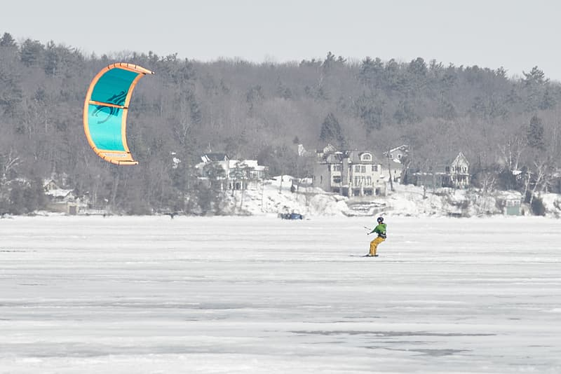 Person in yellow jacket and blue pants holding yellow and red umbrella on snow covered ground