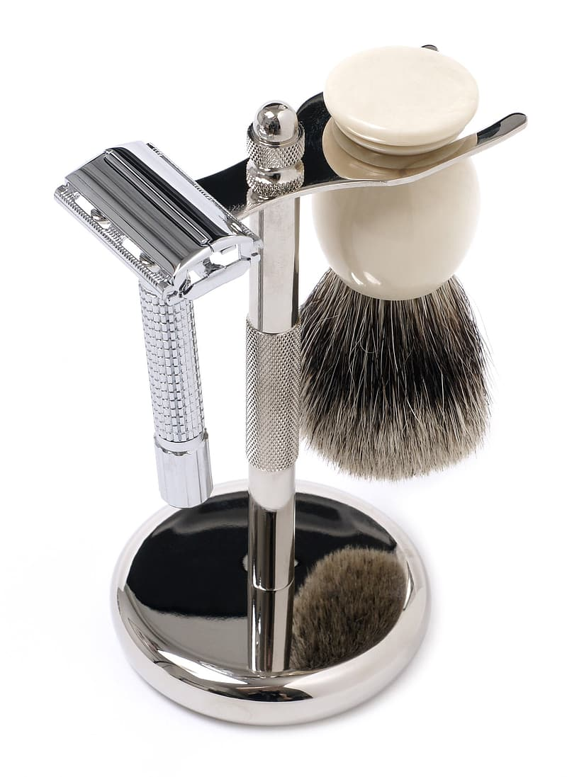 Silver razor and shaving foam brush on silver metal stand