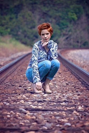 Woman in blue long-sleeved top and jeans on train railings