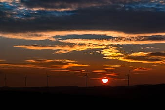 Silhouette of windmills on sunset