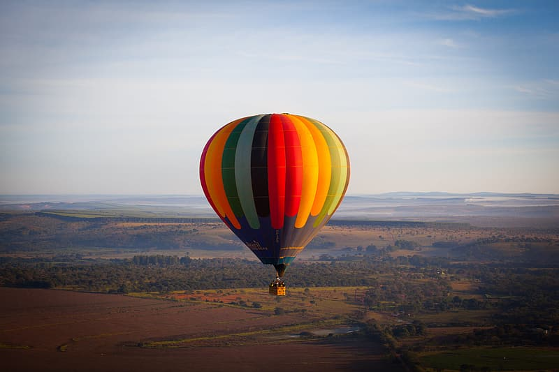 Red, yellow and green hot air balloon on flight