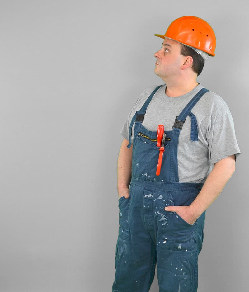 Man wearing blue overalls and orange hard hat