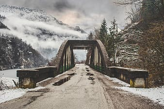Gray concrete bridge near snow covered mountain