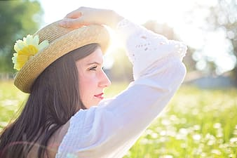 Woman wearing white long-sleeved blouse holding her brown hat with yellow flower