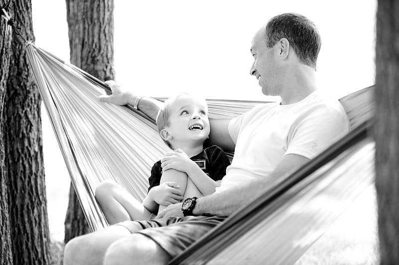 Grayscale photograph of father and son in hammock