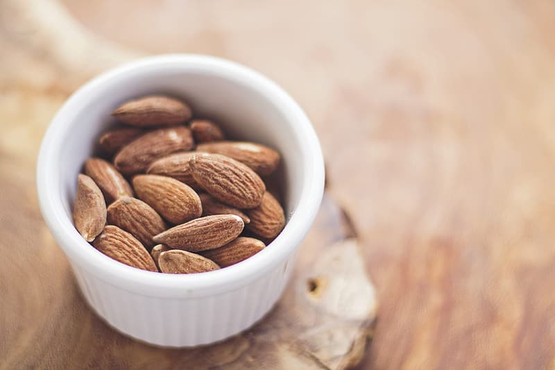 Brown almond nuts in round white ramekin