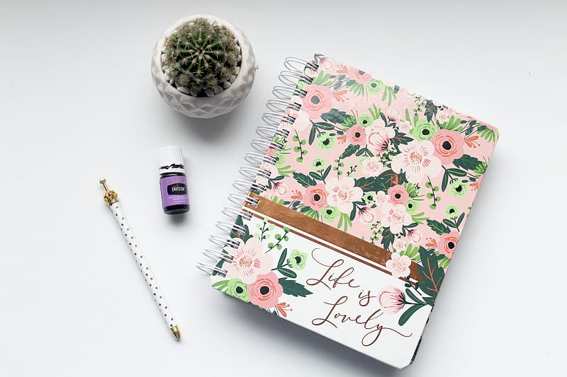 Pink and white floral notebook beside white pen