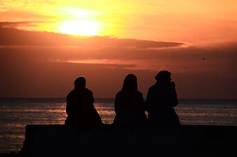 Silhouette of three people sitting near body of water during golden hour