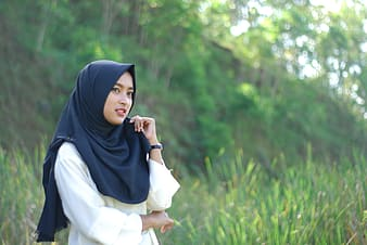 Woman wears black hijab surrounded by green grass during daytime