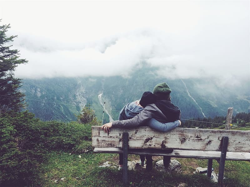 Man and woman sit on bench in front of mountain during daytime