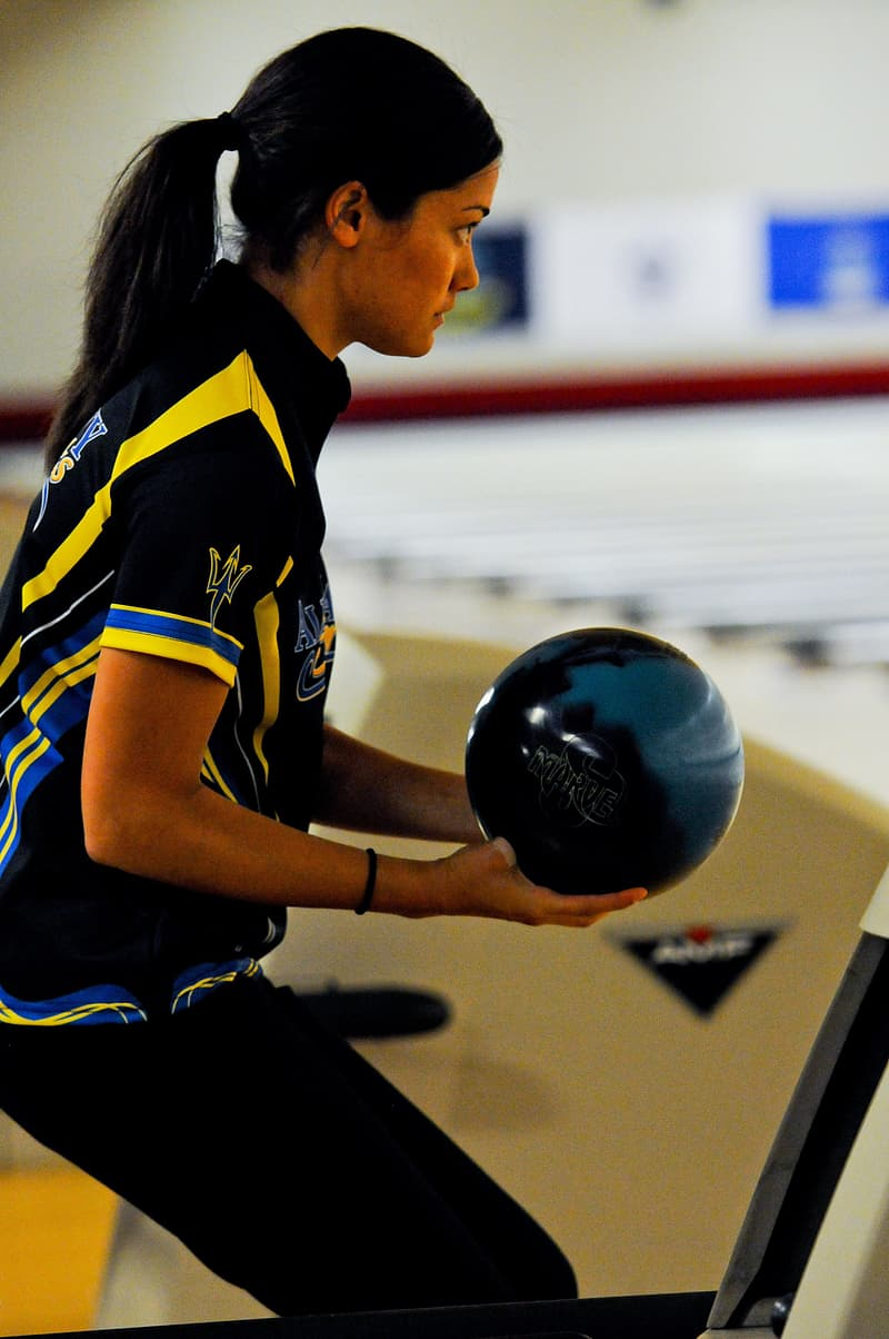 Woman in blue and yellow jersey shirt holding black ball