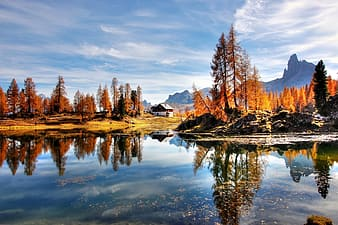 Landscape photography of lake casting reflection of brown rocks, brown leaf trees, and white house