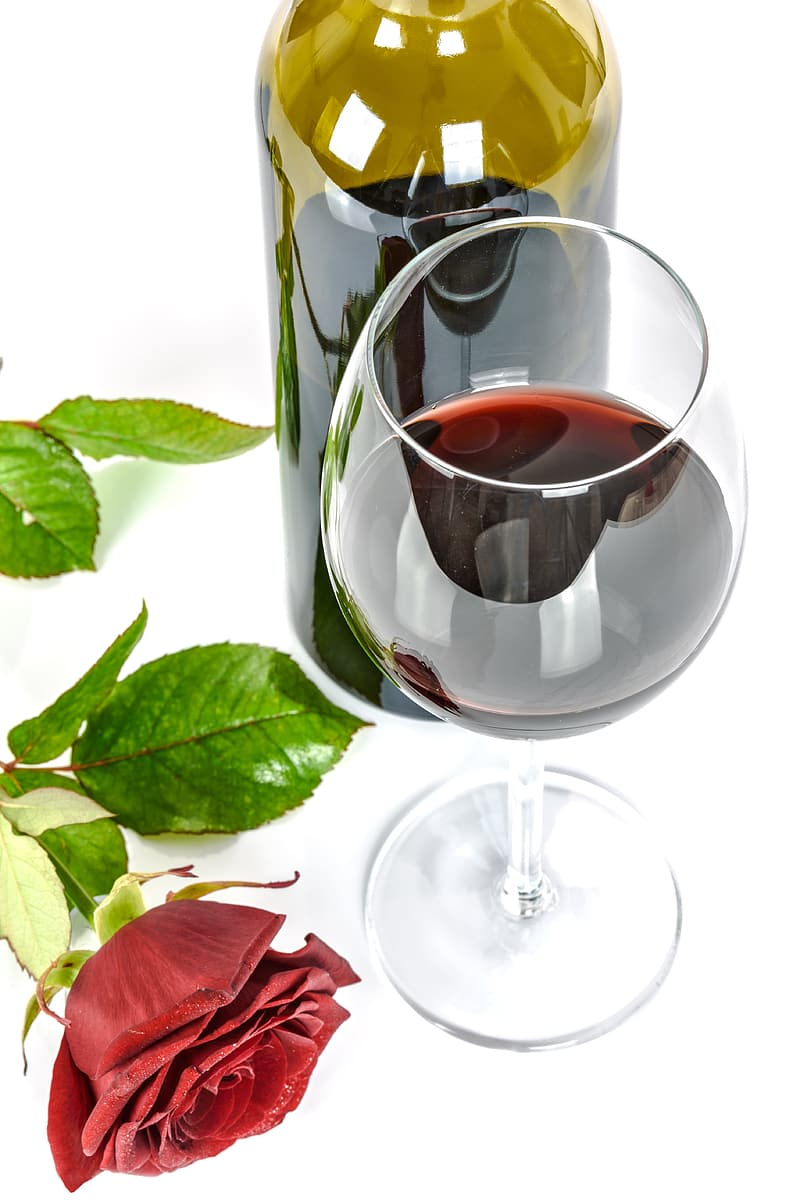 Clear wine glass beside red rose