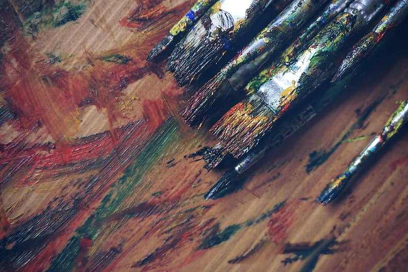 Assorted-color paint brush on brown wooden table