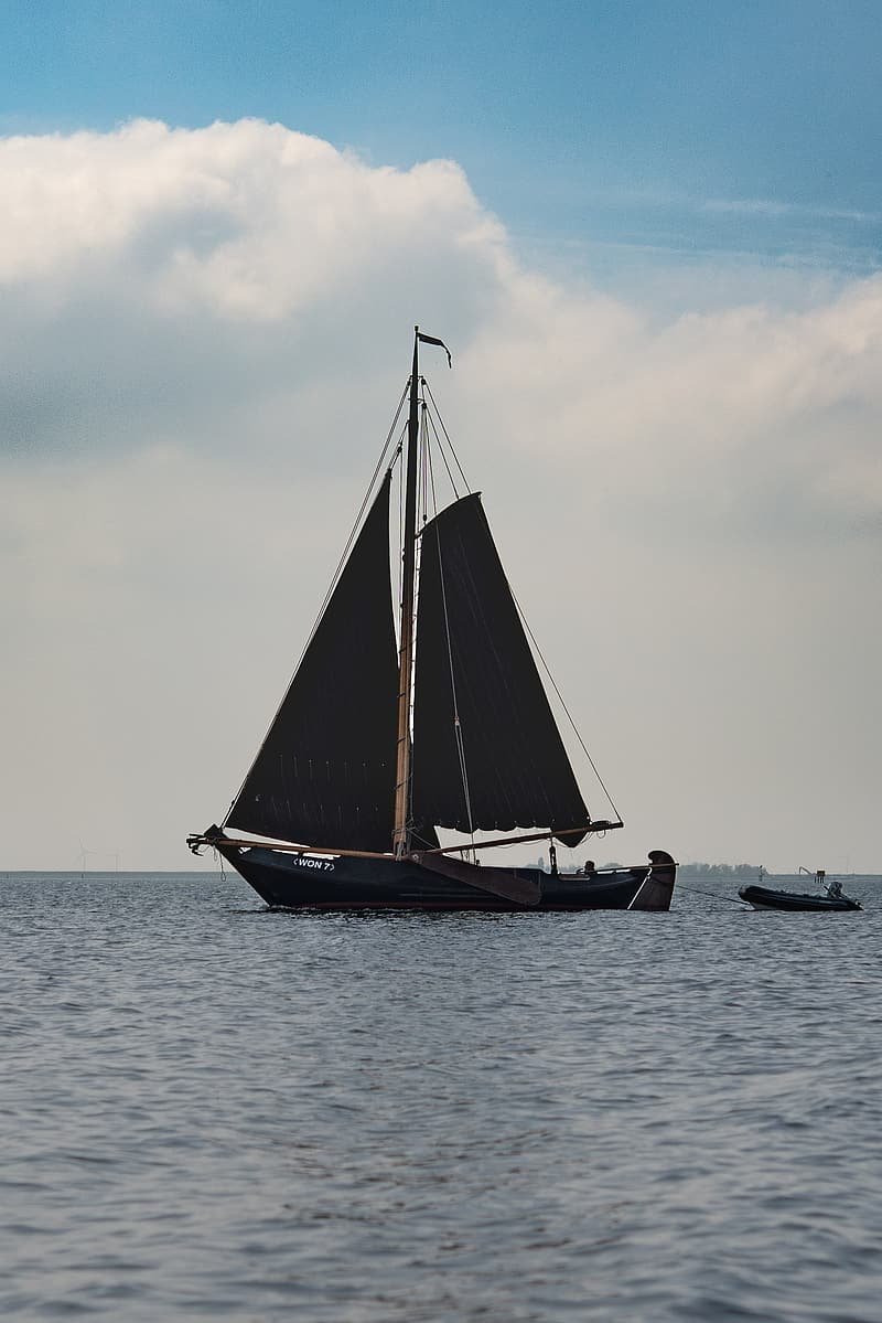 Black and white sail boat on sea under white clouds during daytime