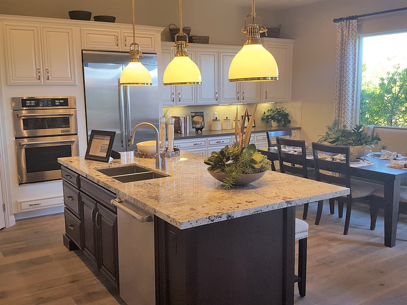 Grey kitchen island with three beige pendant lamps turned on